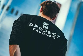 a man showing his back side and wearing a black t-short with project cannabis text on it
