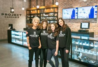 a group of 3 women and 1 man, wearing black Project cannabis t-shirts