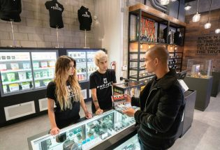 inside store, 2 sellers, man and woman wearing black t-shirts with project cannabis on it and talking to a buyer wearing black jacket